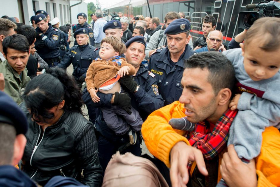 Police help children and mothers to board a train in Nickelsdorf, Austria