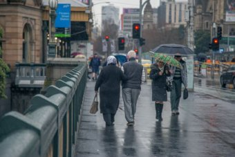 Pedestrians shelter under umbrellas as rain falls in Melbourne.