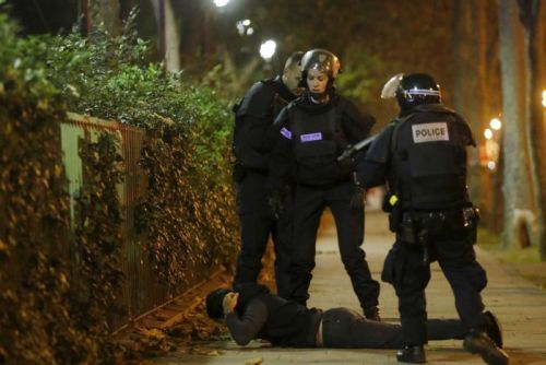 A man lies on the ground as French police check his identity near the Bataclan concert hall