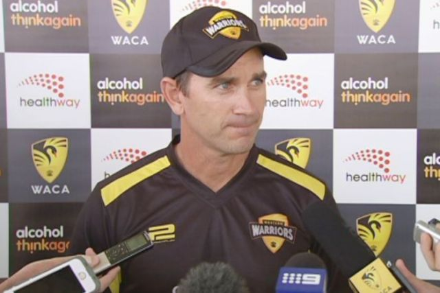 Justin Langer speaks to journalists wearing a Western Warriors shirt and hat.