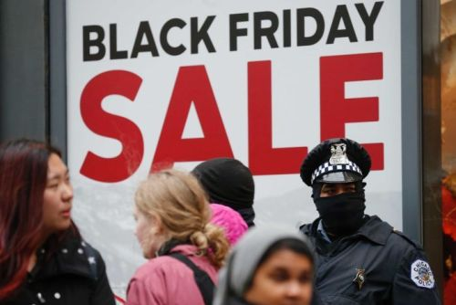 Chicago Police officers stand watch outside a store as shoppers pass by during a protest on Black Friday