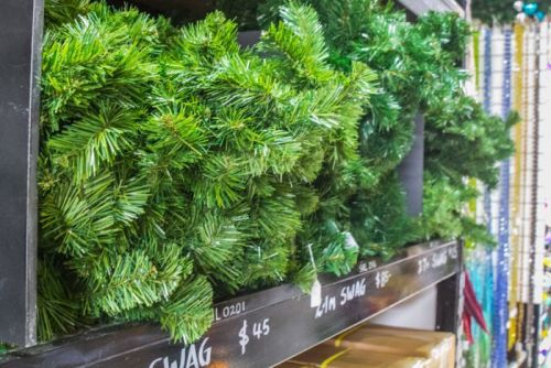Individual Christmas tree branches are stacked in size and length in the prop showroom.