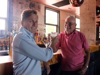 Connections owner Tim Brown (blue shirt) clinks glasses with long-time patron Neil van Zee.