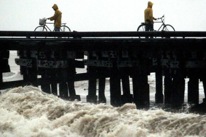 Cyclists watch the floods.