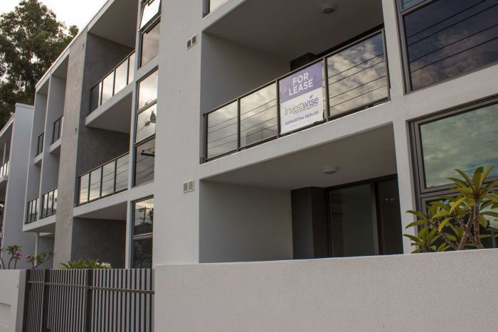 A newly-built apartment building with for lease sign.