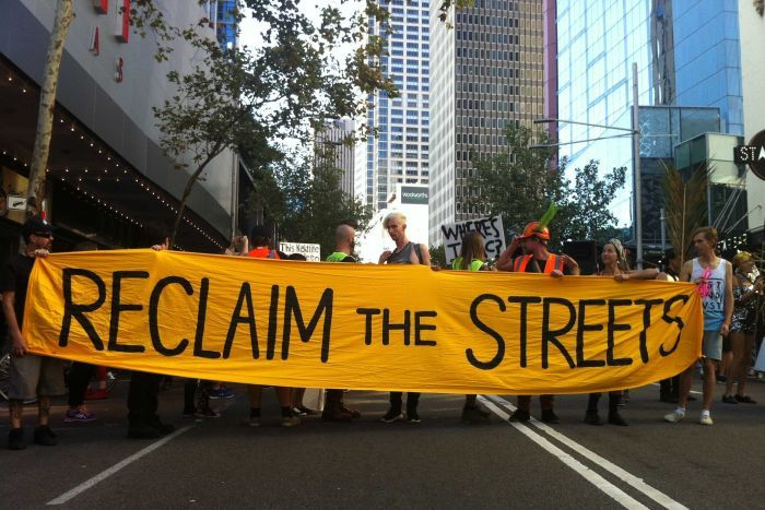 "Protesters hold a sign that reads ""Reclaim the Streets"" outside Sydney's Star City Casino."