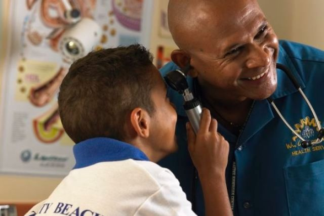 Dr Wenitong has his ear checked by a child