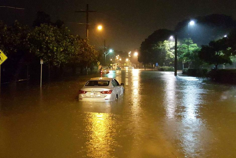 A car in water halfway up its wheels on a flooded street in Kirra on the Gold Coast on Saturday night