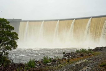 Water flows over the wall of the dam powering the Repulse Power Station.