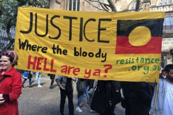 Protesters hold up a placard saying: Justice where the bloody hell are ya?