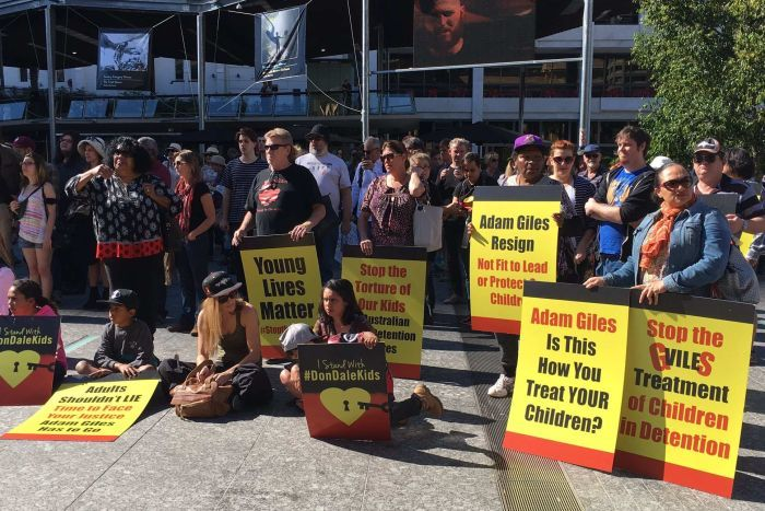 A crowd of people hold signs criticising NT Chief Minister Adam Giles.