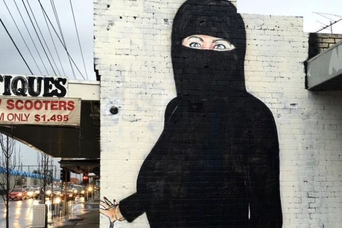 Mural of Hillary Clinton on the side of a building wearing a burqa.