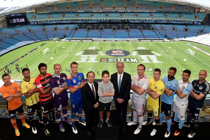 The captains of the A-League clubs pose in a line with a young boy and two men in suits.