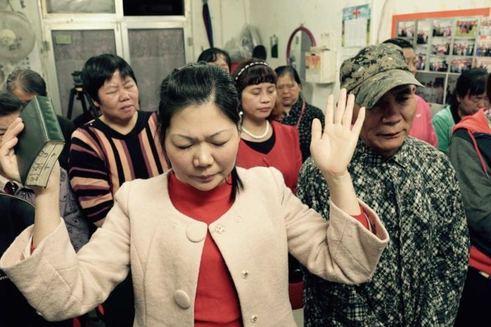 People pray at a small Protestant underground that operates in a shop front in Beijing, China.