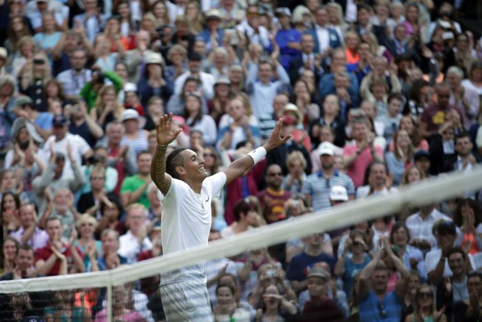 Nick Kyrgios raises his arms in triumph dressed in all white.