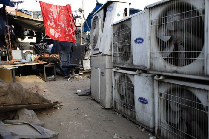 An Indian boy sleeps in scorching heat near an air conditioner shop in New Delhi, India