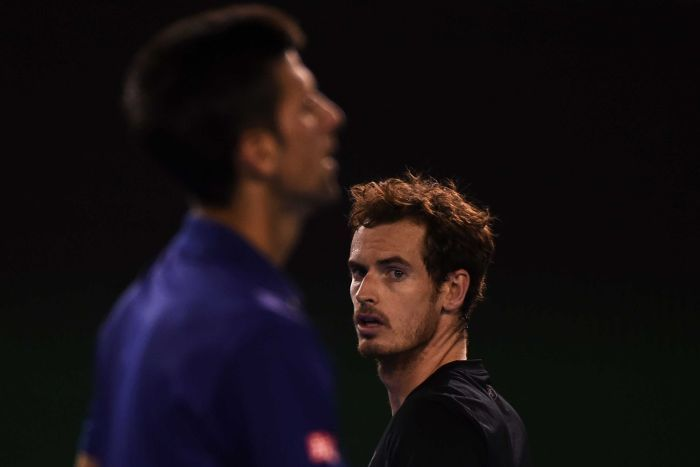 Andy Murray, in focus in the background, looks at Novak Djokovic, blurred in the foreground.