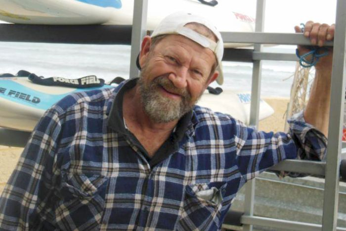 Jeffrey Doyle smiles for a photo wearing a blue flannel shirt and white cap backwards standing with a vehicle on the beach.