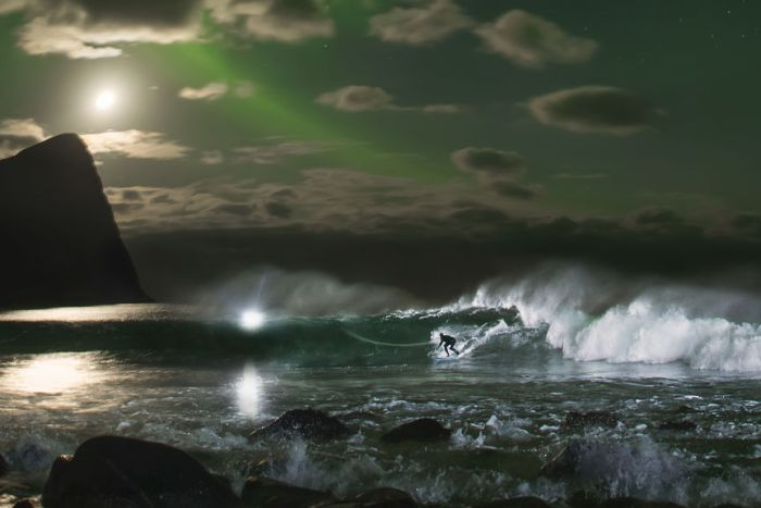 Mick Fanning surfs a wave beneath the Northern Lights in Norway