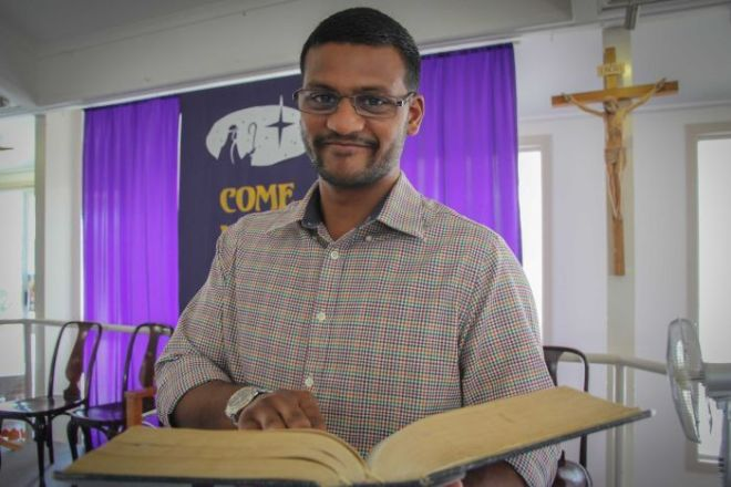25-year-old Ashwin Acharya holds a bible as he looks at the camera.
