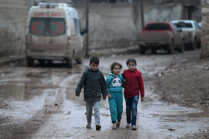 Children walk near a parked ambulance in al-Rai town, northern Aleppo province, Syria, December 27, 2016.