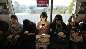 A woman sits in a women's only passenger carriage on the tokyo subway.