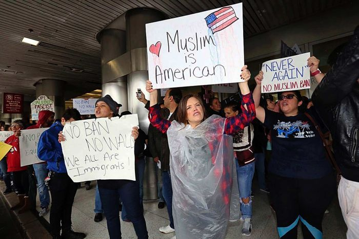 """Protesters hold signs reading """"Muslim is American"""" at Miami airport"""