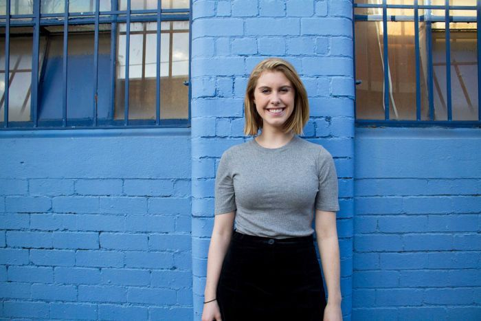 Morgan Koegel standing in front of a blue wall.