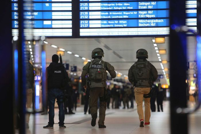 Special forces walk in the main train station in Dusseldorf following the axe attack.