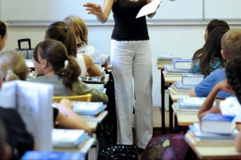 A teacher gives instructions to her pupils in a classroom.