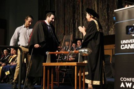 Paul Jenkins walks across the stage to accept his degree.