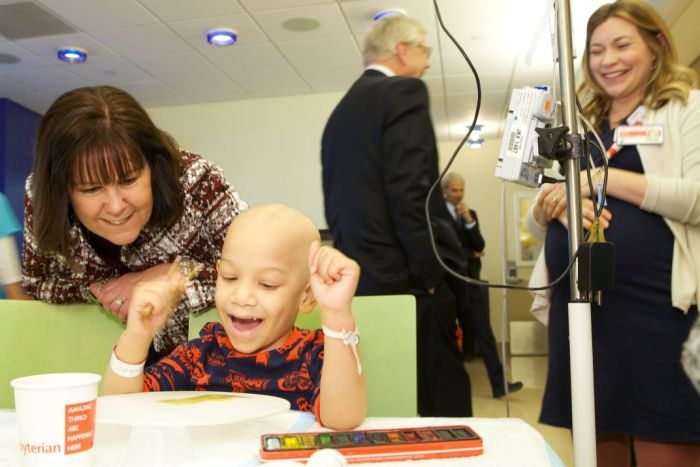 Karen Pence sits with a child who is receiving medical treatment and alternative art therapy treatments at a New York hospital