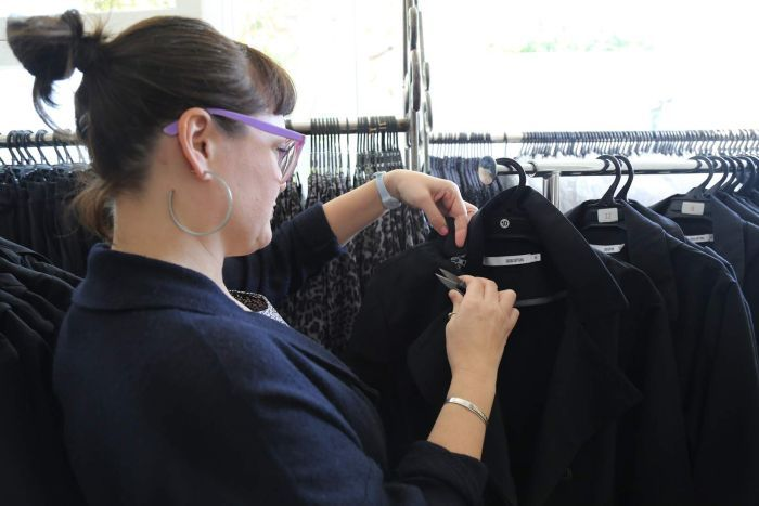 A woman checking a coat on a rack.