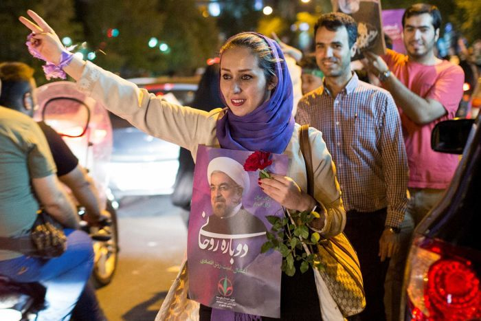 A woman wearing a hijab holds a poster of Iranian President Hassan Rouhani during a campaign rally in Tehran, Iran.