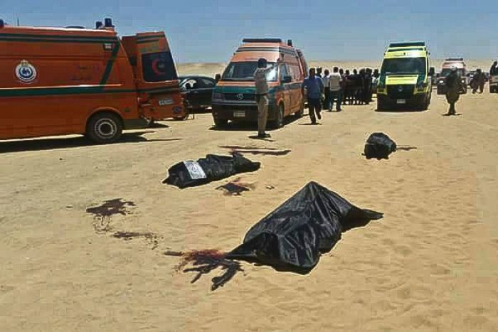 Three bodies lie covered in the desert in front of ambulances and bystanders.