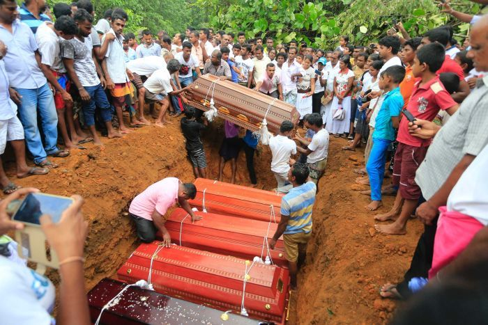 Sri Lankan villagers prepare to bury victims of a landslide at a cemetery.