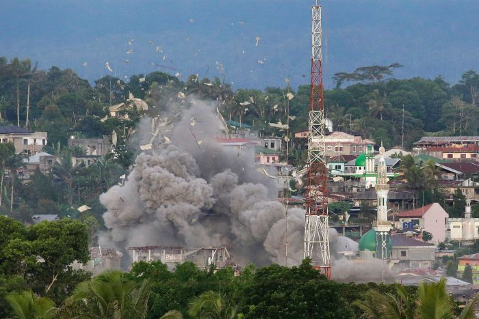 Debris flies in the air as Philippine Air Force fighter jets bomb suspected locations of Muslim militants in Marawi.