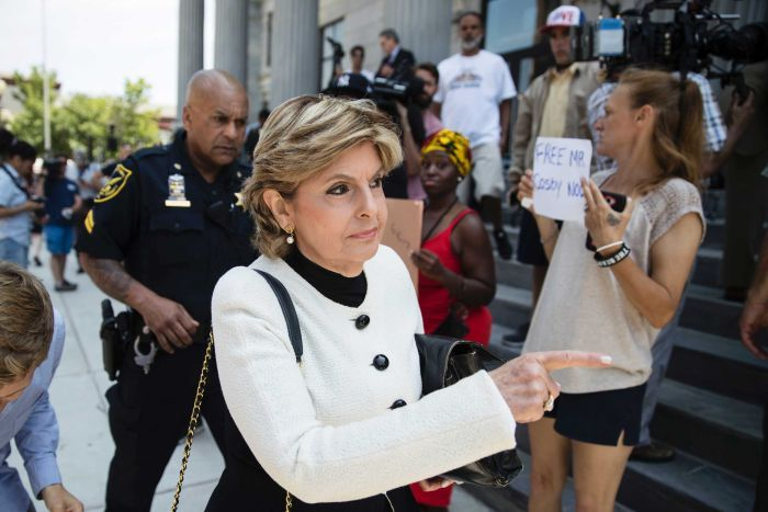 Celebrity lawyer Gloria Allred walks past women holding signs supporting Bill Cosby outside a Pennsylvania courthouse.