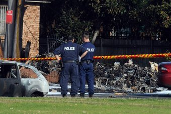 Police inspect the burnt wreckage of a light plane
