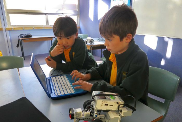 Two male primary school students look at a compute screen in a classroom with a small robot on the table near them