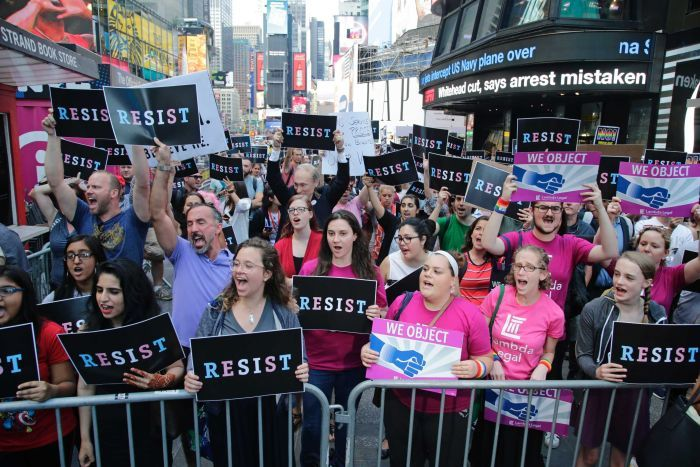 Protesters chant holding signs that read 'RESIST' and 'WE OBJECT' in Times Square, New York.