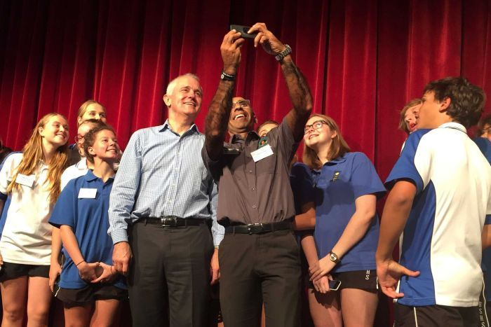 Prime Minister Malcolm Turnbull posing for a selfie with a group of students with a red velvet curtain the background.