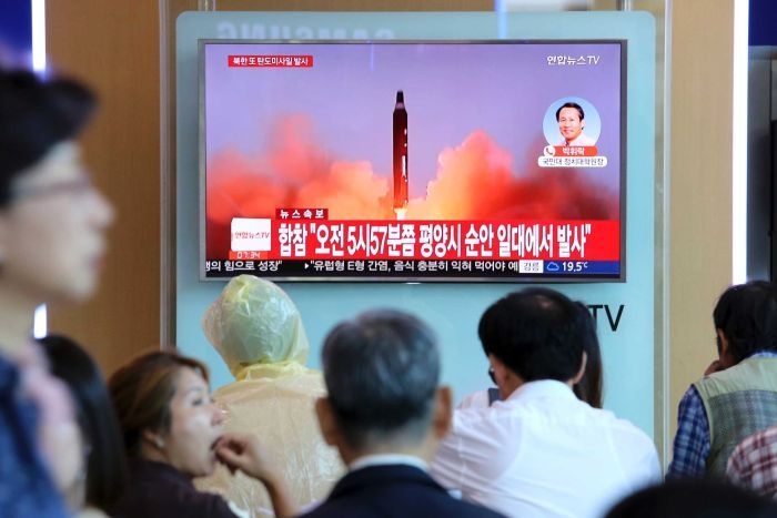 A missile launch is seen on a TV screen as a crowd of people watches in a train station.