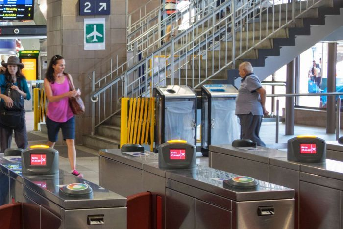 Two women walk past see-through bins at Circular Quay train station in Sydney.