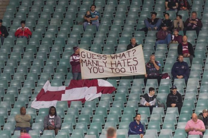 Manly fans hold a sign reading 'GUESS WHAT? MANLY HATES YOU TOO!!!' in the stands before a game.