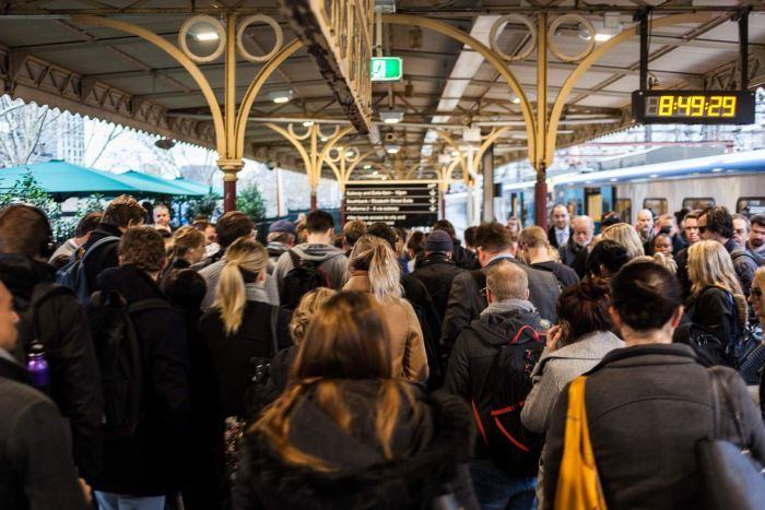 Commuters crowd on a platform at Flinders Street Station.