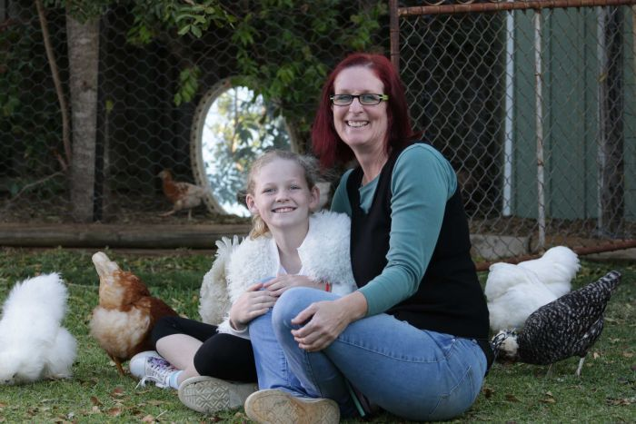 Little girl in a white fluffy jacket and her mum next to her sit in a yard among chickens