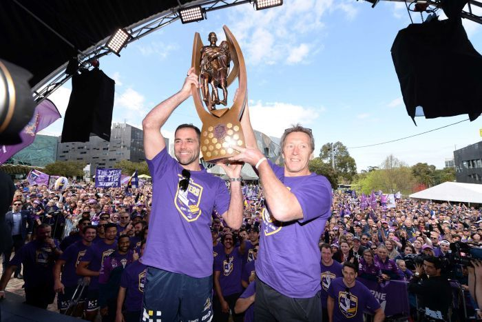 Cameron Smith and Craig Bellamy lift the premiership trophy in front of Storm fans