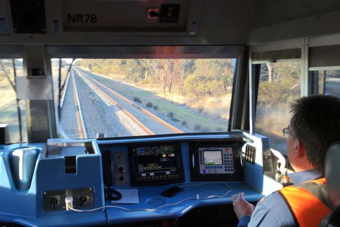 The view from inside the cab of a freight train.