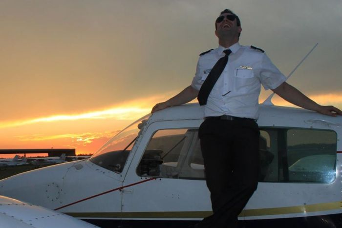 Pilot leaning on small plane and laughing